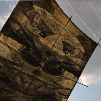 Japanese paper kite printed with a face-like image with the sky in the background