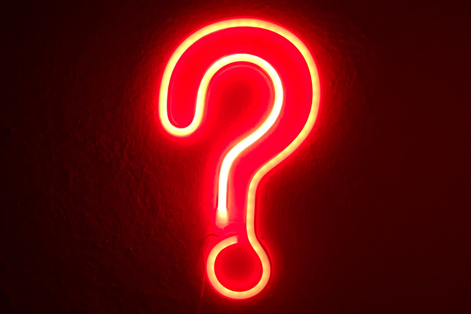 Neon light in shape of a question mark. Photo by Simone Secci on Unsplash