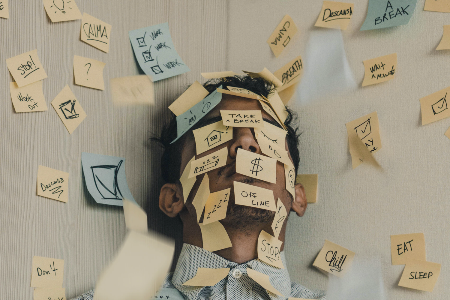 Man covered in sticky notes while leaning against the wall.
