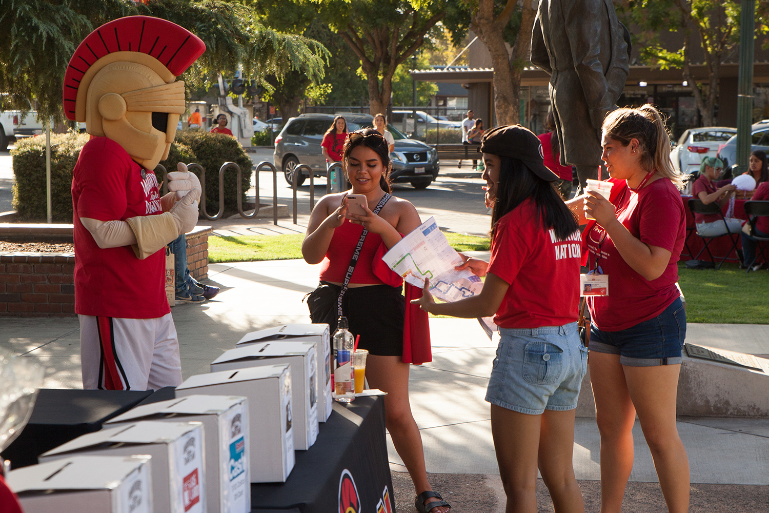 Three female students conversing with Titus mascot.