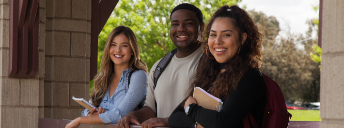 Three students smile for photo.