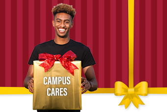 "student holding a gift box that reads ""Campus Cares"""