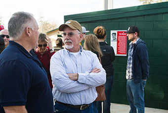 Players from the Stanislaus State 1976 Division III National Champion team reminisce outside the Warrior Field dugout, moments after the unveiling of a plaque commemorating the career of head coach Jim Bowen.