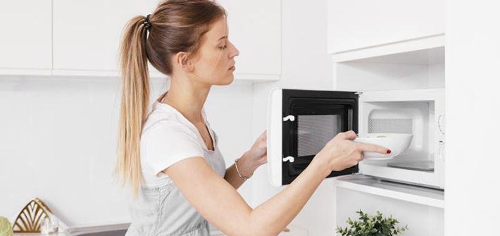 Woman placing a bowl into a microwave.