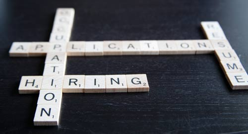 Scrabble pieces spelling out hiring, resume, application, and occupation.