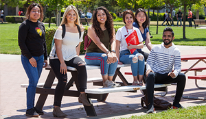 group of diverse students sitting together on campus bench