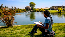 students sitting outside by the pond studying