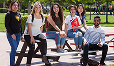 students sitting on benches on campus