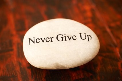 never give up written on a rock