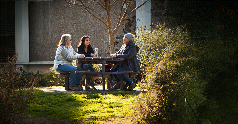 Wendy Olmstead, Ashley Camarena Morales and Emma Denison enjoy a conversation next to Village Lake