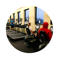 Three students use exercise equipment.