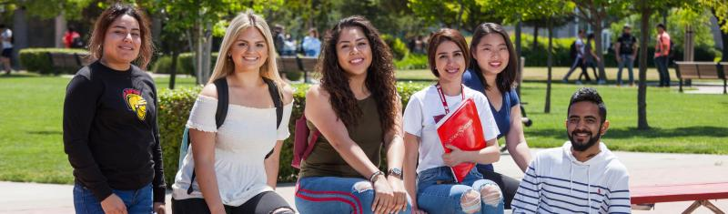 Group of five students sit a bench and smile.