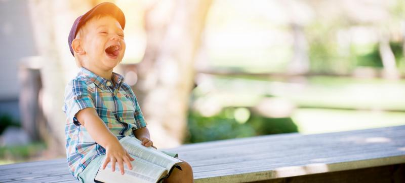 Special needs boy sitting on a bench with a book