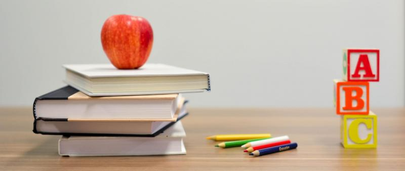 Graphic of apple on stacked books, color pencils, and ABC blocks on desk