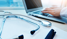 Photo of a laptop and a stethoscope for the Online RN-BSN program