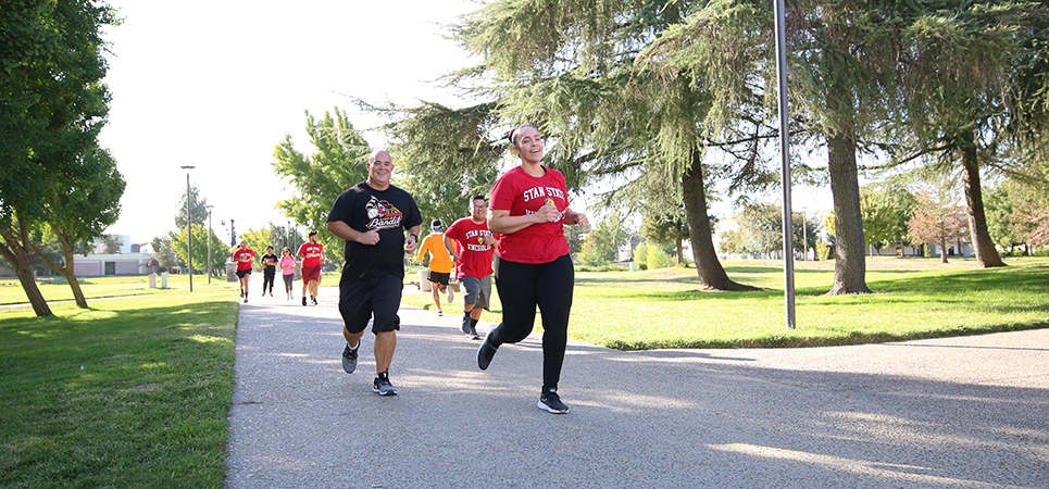 Kins Fit students and Dr. Jeff Bernard running in front of Fitzpatrick Arena