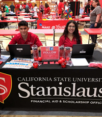 Student assistants table at an event with financial aid information