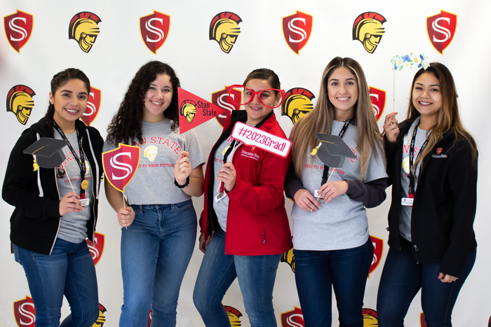 Group of students posing with photo booth props