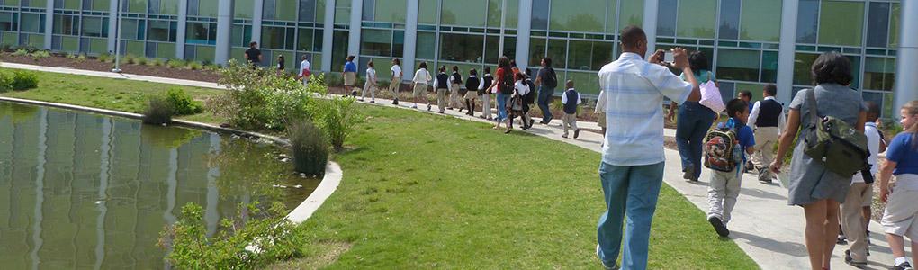 Schoolchildren walking between pond and Naraghi Hall of Science
