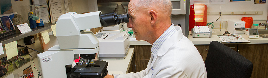 Man looking into microscope in student health center