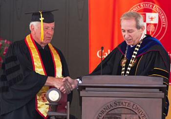 Jim Toepfer, Class of 1964, is recognized as a Golden Grad by President Joseph F. Sheley during the May 30 commencement ceremony.