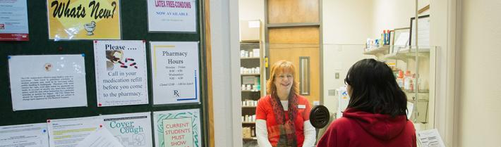 Pharmacist speaking with a student at the pharmacy window