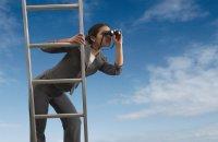 Woman on a ladder looking through binoculars