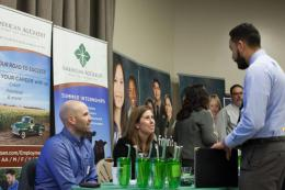 male student speaking to employers at career fair