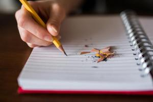 hand holding pencil writing in paper notebook