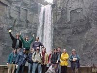 research group posing in front of waterfall