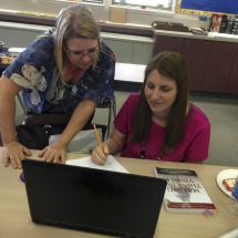 Teacher helping student with writing