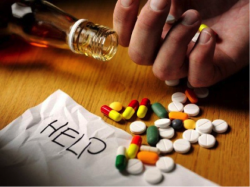 "This is an image of a bottle of alcohol and a hand holding various pills with a note that reads ""help."""