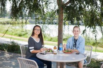 Photo of two students eating together.