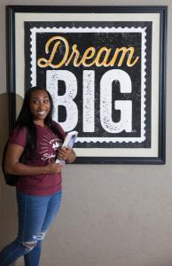 girl in front of Dream Big poster