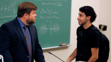 student talking to professor in classroom