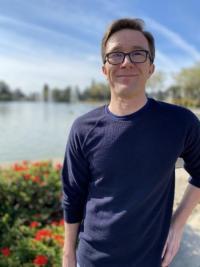 Dr. Curtis Pro posing affront of pond