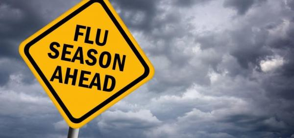 Sign stating Flu Seasn Ahead with a cloudy background.