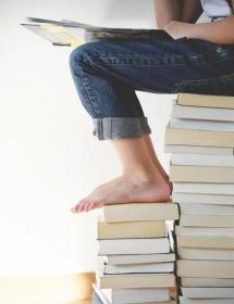Graphic of a student sitting on a stack of books while reading a book