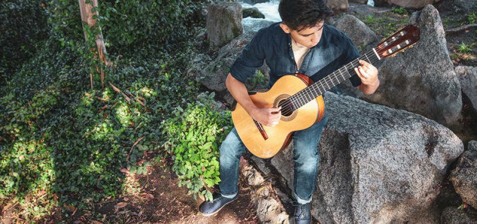 Adrian Vega with guitar outdoors