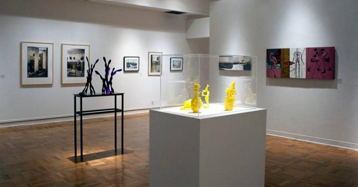 Installation view of the University Art Gallery. Sculptures on pedestals and paintings and photos on the walls.