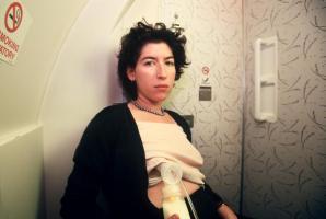 A woman uses a breast pump in an airplane bathroom