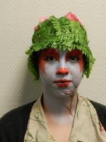 student with orange and white face paint and a green hat