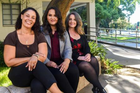 Three women who graduated from the accelerated bachelor's degree program sit outside at the Stan State Stockton Center campus.