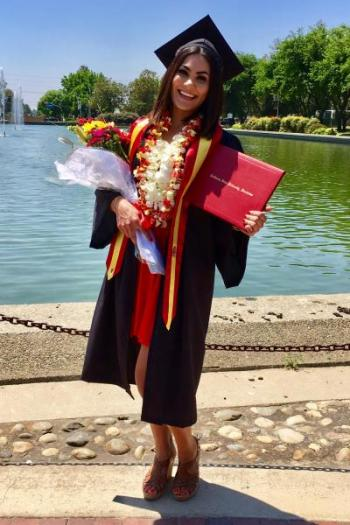Cody Yamada poses in her graduation gown at the University reflecting pond.