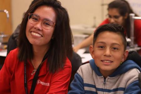 Stan State student Serene Aman smiles beside 7th-grader Miael Guevara in the Dutcher lab