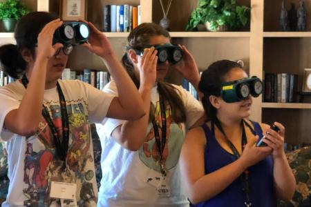 Three high school students try on googles that make viewing difficult, as if they had a complication of diabetes.