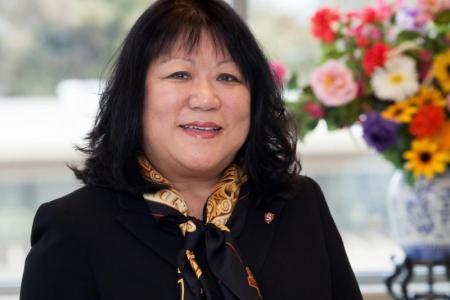 President Ellen Junn smile beside a vase of flowers