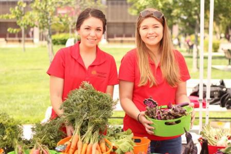 Students sell campus-grown vegetables at farmers market on Quad