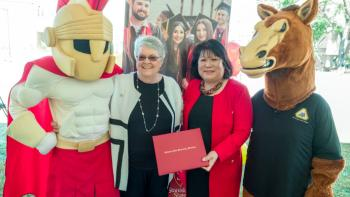 Stan State mascot Titus the Warrior, SJDC President Kathy Hart, Stan State President Ellen Junn and SJDC mascot Fierce the Mascot pose at the agreement celebration.
