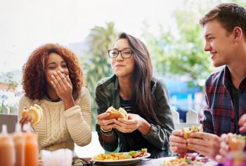 Photo of three students eating together.
